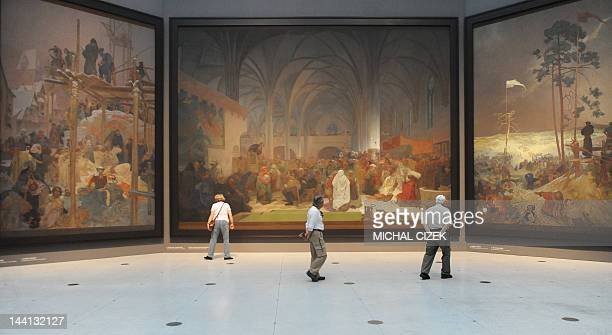 """Visitors look at paintings of the """"Slav Epic"""", a cycle of 20 allegories tracing the history of the Slavic people and inspired in part by mythology,..."""