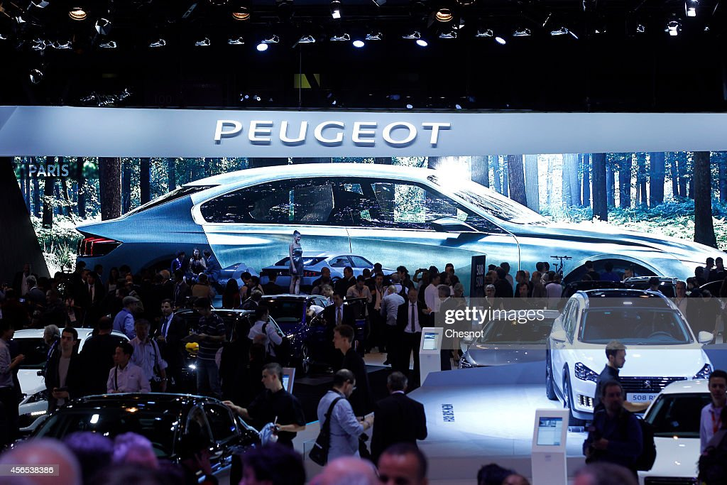 Visitors look at Peugeot automobiles, produced by PSA, during the press day of the Paris Motor Show on October 02, 2014, in Paris, France. The Paris Motor Show will showcase the latest models from the auto industry's leading manufacturers at the Paris Expo exhibition centre.