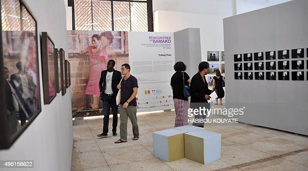 Visitors look at photographs during the opening of the 10th edition of the Bamako Encounters African Photography Biennale in Bamako on October 31...