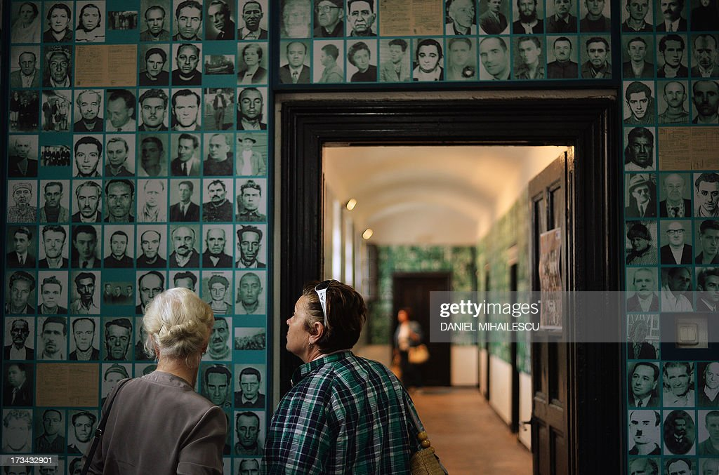 Visitors look at photographs of victims of the communist repression in Romania at a memorial, a former communist era prison in Sighetu Marmatiei on July 13, 2013. Former dissidents and political prisoners gathered in Romania on July 14, 2013 at a museum commemorating those who suffered abuses under communism, set up 20 years ago at the site of a prison where scores died.