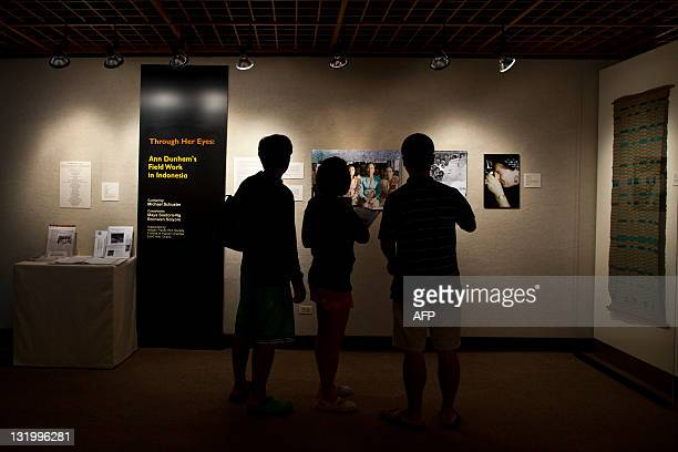 Visitors look at photographs taken during fieldwork in Indonesia by S Ann Dunham US President Barack Obama's late mother during an exhibition at a...