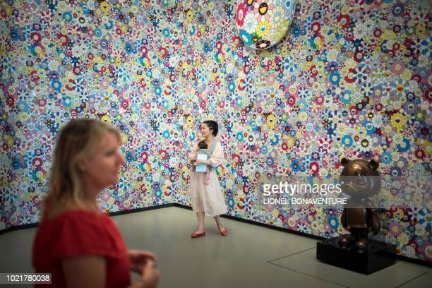 Visitors look at pictorial works in the Kawaii space by Japanese artist Takashi Murakami at The Louis Vuitton Foundation in Paris on August 22 2018 /...