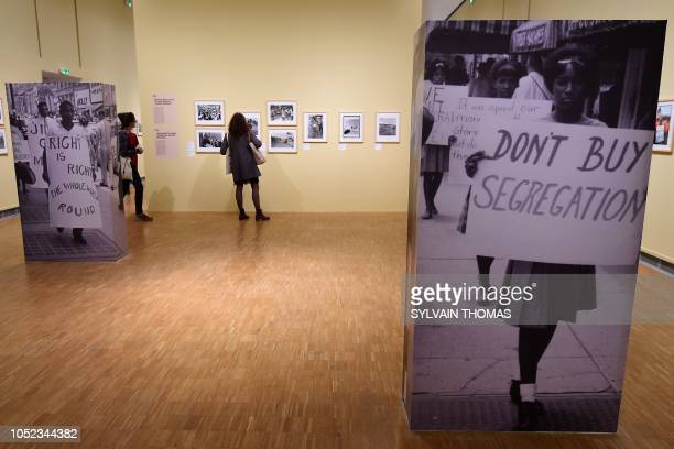 Visitors look at pictures at the exhibition entitled 'I am a man' Photographs and struggles for civic rights in the south of the USA 19601970 at the...