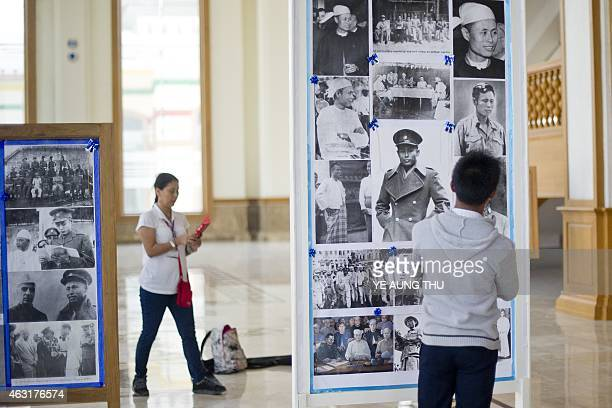 Visitors look at pictures of General Aung San inside the theatre hall in parliament in NayPyiDaw on February 11 2015 Celebrations will mark a hundred...