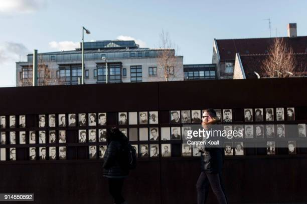 Visitors look at pictures of people who died at the border at the Berlin Wall memorial at Bernauer Strasse on February 5, 2018 in Berlin, Germany....