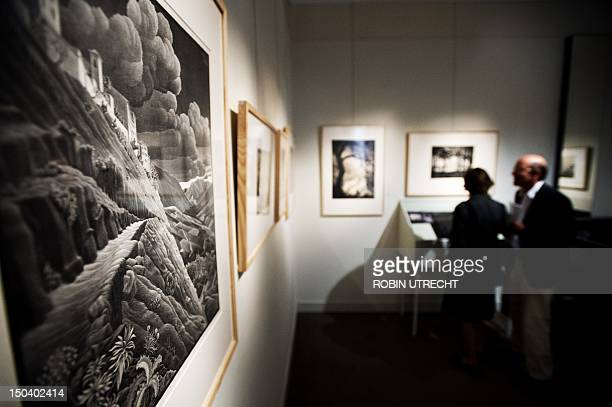 Visitors look at pieces by world famous Dutch graphic artist MC Escher at Soestdijk Palace in Baarn on August 16 2012 The exhibition ' MC Escher...