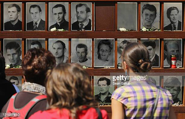 Visitors look at portraits of people who were killed trying to cross from east to west across the Berlin Wall on the 50th anniversary of the...