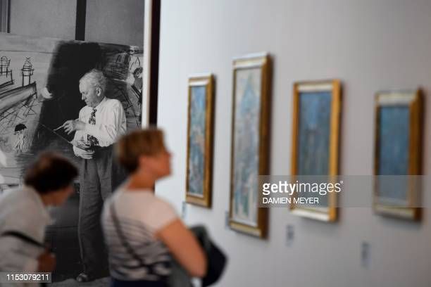 Visitors look at Raoul Dufy paintings with Dufy's photograph seen in the background at MuMa Andre Malraux Museum of Modern Art in Le Havre on June 28...