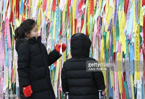 Visitors look at ribbons wishing for peace and reunification of the Korean Peninsula on a military fence at Imjingak peace park, near the...