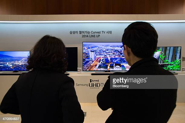 Visitors look at Samsung Electronics Co curved Ultra High Definition televisions displayed at a media event in Seoul South Korea on Thursday Feb 20...