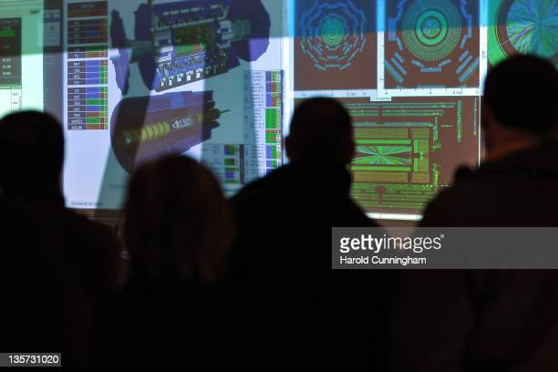 CERN visitors look at screens in the ATLAS LHC control room on December 13 2011 in Geneva Switzerland The European Organization for Nuclear Research...