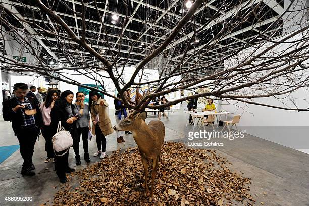 Visitors look at sculpture 'Untitled' by Kim Myeongbeom made of deer taxidermy leaves and branches on the preview day of Art Basel on March 13 2015...
