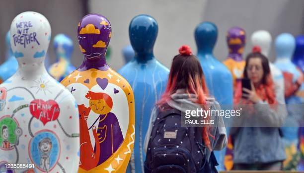 Visitors look at sculptures as part of 'Gratitude', a public art installation, created by global public art producers Wild in Art, to honour and pay...