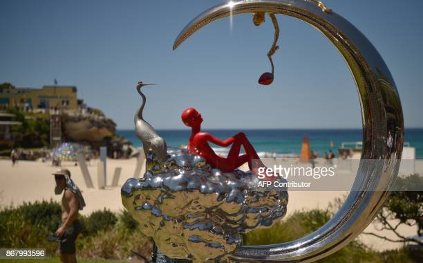 Visitors look at sculptures on display on Tamarama Beach as part of the Sculpture by the Sea exhibition in Sydney on October 30 2017 Celebrating it's...