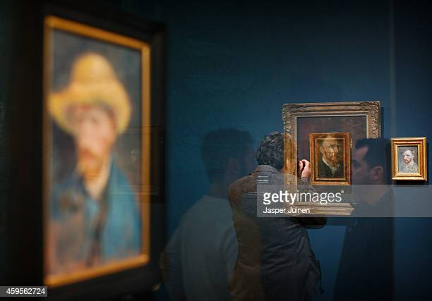 Visitors look at self portraits of Dutch PostImpressionist painter Vincent van Gogh on the ground floor of the Vincent van Gogh museum on November 25...