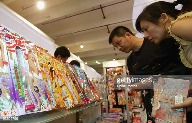 Visitors look at sex toys at the AdultCare Expo at the International Exhibition Center on July 29 2005 in Shanghai China The expo featured the latest...