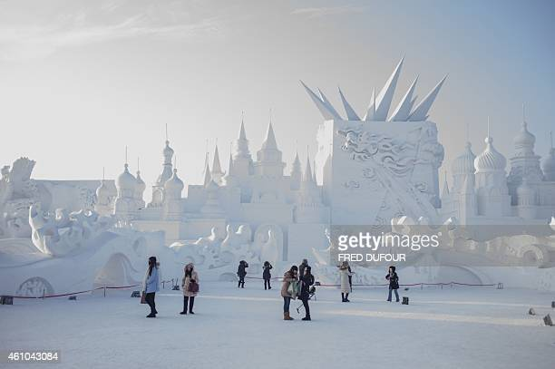 Visitors look at snow sculptures during the 16th Harbin International Ice and Snow Festival in Harbin northeast China's Heilongjiang province on...