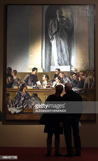 Visitors look at Soviet artist Grigory Shegals painting Leader Teacher and Friend displayed in the exhibition Romantic Realism Soviet Art of 19251945...