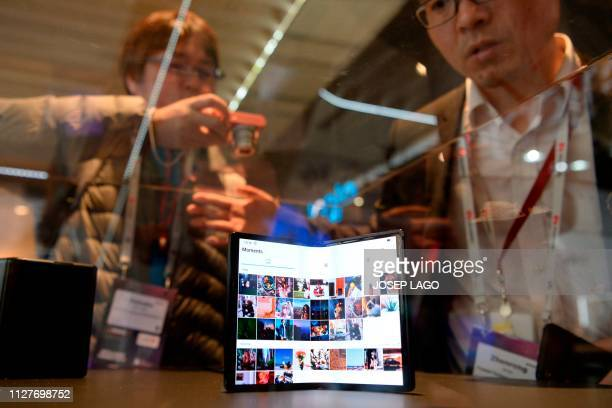 Visitors look at TCL's DragonHinge foldable products at the Mobile World Congress in Barcelona on February 27 2019 Phone makers will focus on...