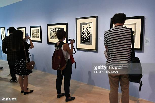 Visitors look at the art exhibition 'Journey to Infinity Escher's World of Wonder' which showcases the works of world famous graphic artists Maurits...