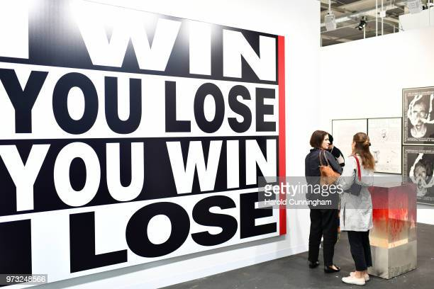 """Visitors look at the artwork of Barbara Kruger """"Untitled"""" during the press preview for Art Basel at Basel Messe on June 13, 2018 in Basel,..."""