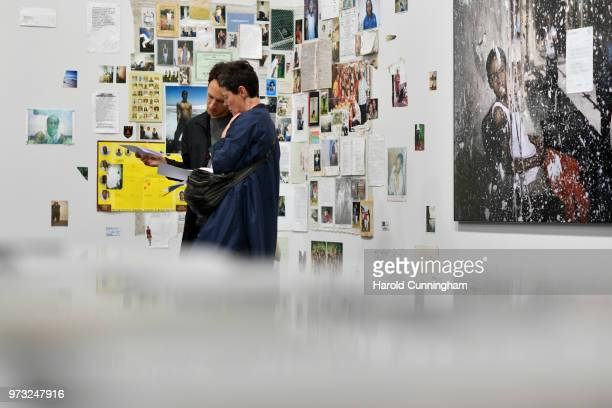 Visitors look at the artwork of Mikhael Subotzky and Patrick Waterhouse 'Ponte City' during the press preview for Art Basel at Basel Messe on June 13...