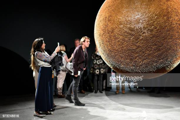 Visitors look at the artwork of Robert Longo 'Death Star II' during the press preview for Art Basel at Basel Messe on June 13 2018 in Basel...