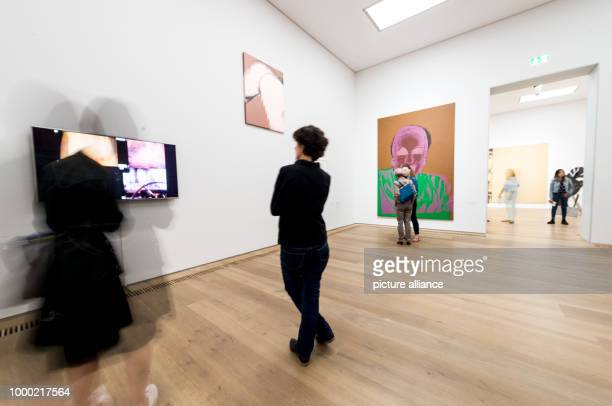 Visitors look at the artwork shown in the exhibition Pop Pictures People in Munich Germany 29 June 2017 The exhibition aims to contrast works of Andy...