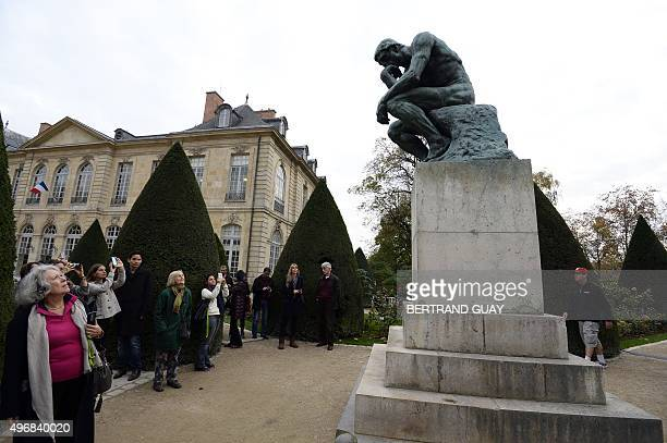 Visitors look at the bronze sculpture 'The Thinker' by French sculptor Auguste Rodin in the garden of the Hotel Biron housing the Musee Rodin in...