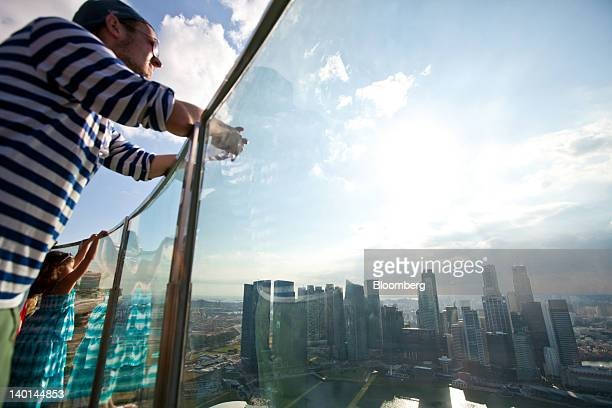 Visitors look at the central business district skyline from the SkyPark atop Marina Bay Sands in Singapore on Tuesday Feb 28 2012 The number of...