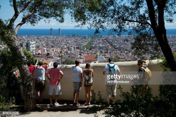 Visitors look at the city's panorama at Park Guell in Barcelona on August 10 2017 Spanish activists in recent weeks have launched initiatives against...