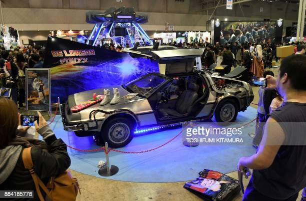 Visitors look at the DeLorian time machine from the 1985 film 'Back to the Future' on display at Tokyo Comic Con 2017 at Makuhari Messe in Chiba on...