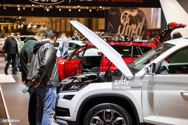Visitors look at the engine of a Skoda car at the Essen Motor Show on December 1 2017 in Essen Germany The Essen Motor show is celebrating its 50th...