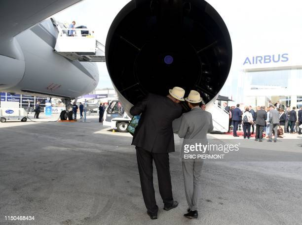 Visitors look at the engine of the Airbus A330 MRTT multirole tanker aircraft while visiting the Airbus static display at the International Paris Air...