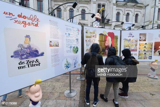 Visitors look at the exhibition of Swiss comic series 'Titeuf' for its 25th anniversary in front of the town hall on the occasion of the 45th edition...