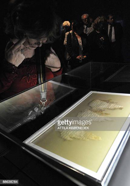 Visitors look at the exhibition� s most valuable and most fascinating artefact a piece of the 2000yearold Dead Sea Scrolls in the Fine Arts Museum of...