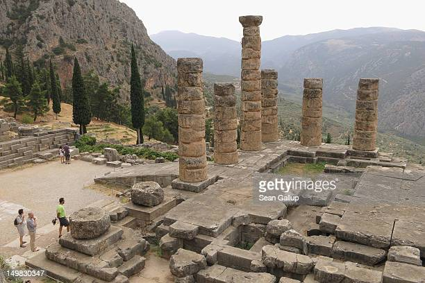 Visitors look at the former Palace of Apollo where the oracle once prophesized the future at the ancient archeological site of Delphi on August 2...