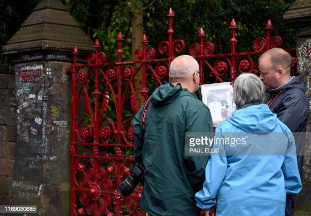 Visitors look at the gates to Strawberry Field in Liverpool northwest England on September 18 2019 Beatles fans can now take a trip through the...