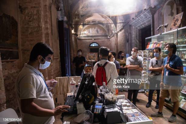 Visitors look at the gift shop of the Chora Church Museum, the 11th century church of St. Savior's souvenir shop on August 21, 2020 in Istanbul,...