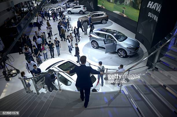Visitors look at the Haval SUV exhibition at the Beijing Auto Show in Beijing on April 25 2016 Global carmakers gathered in Beijing on April 25 to...