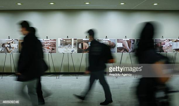 Visitors look at the images of dead bodies at the UN headquarters in New York on March 12 2015 Images of torture carried out by the Syrian regime...