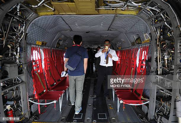 Visitors look at the interior of a Boeing CH47 Chinook helicopter on display by the Singapore Air Force during the Singapore Airshow on February 17...
