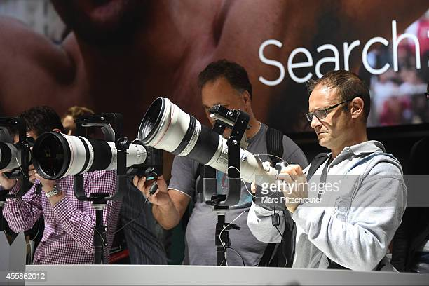 Visitors look at the latest Canon digital cameras at the 2014 Photokina trade fair on September 21 2014 in Cologne Germany Photokina is the world's...