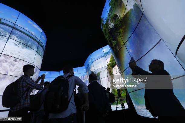 Visitors look at the LG Oled Screen installation at the 2018 IFA consumer electronics and home appliances trade fair during the fair's press day on...