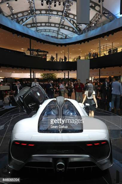 Visitors look at the MercedesAMG Project One car which Mercedes has dubbed a 'hypercar' due to its Formula One technology at the 2017 Frankfurt Auto...