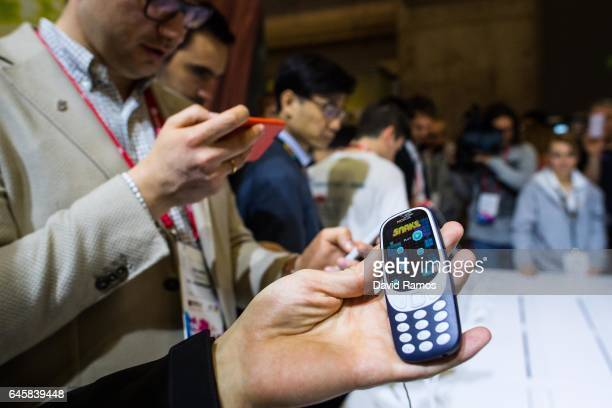Visitors look at the new Nokia 3310 during the Mobile World Congress 2017 on the opening day of the event at the Fira Gran Via Complex on February 27...