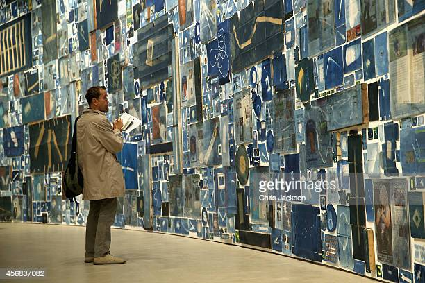 Visitors look at the new Walead Beshty commission at The Curve, Barbican Centre showing from the 9 October 2014 until the 8th February 2015 at...