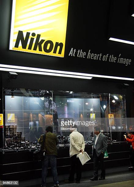 Visitors look at the Nikon Corp booth at the Photo Imaging Expo in Tokyo Japan on Wednesday March 19 2008 Nikon Corp is the world's secondbiggest...