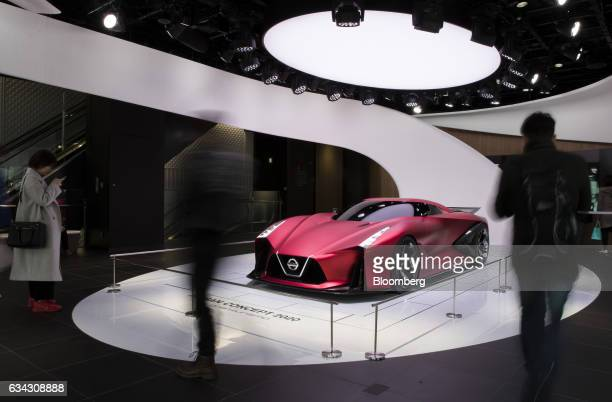 Visitors look at the Nissan Motor Co Concept 2020 Vision Gran Turismo concept vehicle displayed at the company's Nissan Crossing showroom in the...