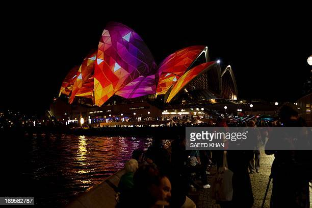 Visitors look at the Opera House being lit up by a projection during Vivid Sydney the annual festival of light music and ideas in Sydney on May 28...